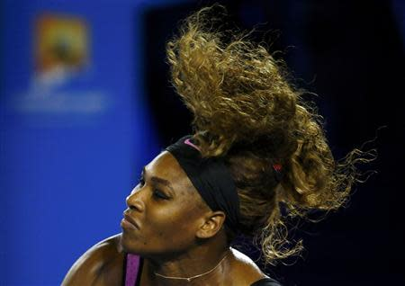 Serena Williams of the United States serves to Ashleigh Barty of Australia during their women's singles match at the Australian Open 2014 tennis tournament in Melbourne January 13, 2014. REUTERS/David Gray