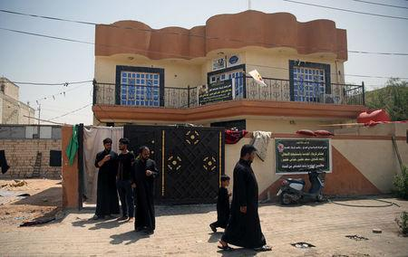 Relatives of Saad Khudair Abbas, who was killed with a group of youth by Islamic State militants at Kirkuk road, are seen outside a house in Kerbala, Iraq July 5, 2018. Picture taken July 5, 2018. REUTERS/Abdullah Dhiaa al-Deen