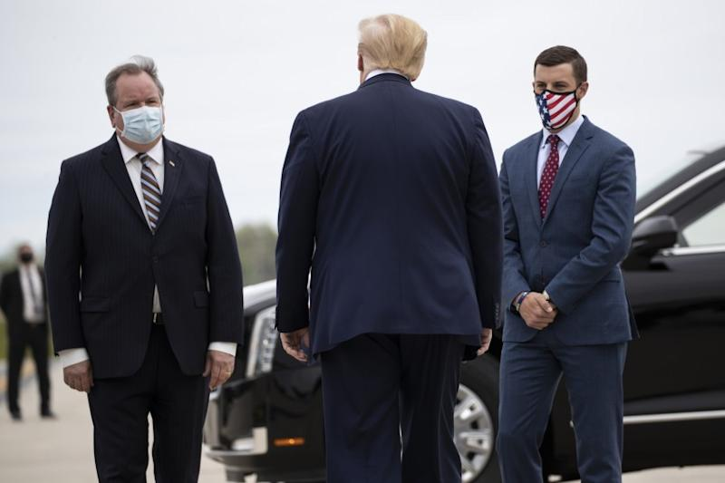 President Trump is greeted at at Detroit airport by Kurt Heise, left, supervisor of Plymouth Township, and Speaker Lee Chatfield of the state House of Representatives.