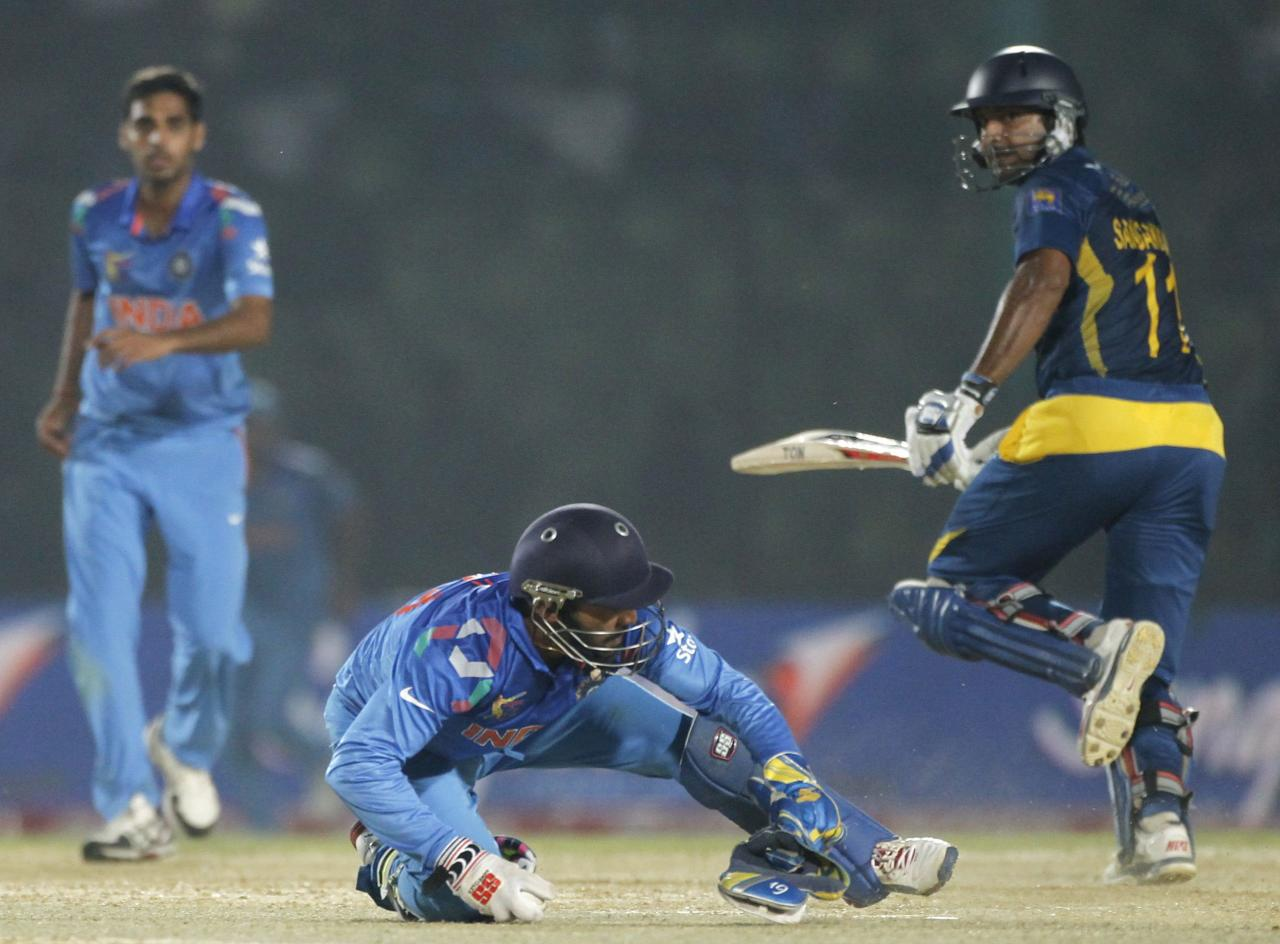 Sri Lanka's Kumar Sangakkara (R) runs between the wickets as India's wicketkeeper Dinesh Kartik jumps to catch a ball during their Asia Cup 2014 one-day international (ODI) cricket match in Fatullah February 28, 2014. REUTERS/Andrew Biraj (BANGLADESH - Tags: SPORT CRICKET)