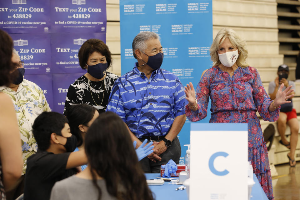 Hawaii Gov. David Ige, center, his wife Dawn Amano-Ige, left, and first lady Jill Biden, right, tour a COVID-19 vaccination clinic at a high school in Waipahu, Hawaii, Sunday, July 25, 2021. (AP Photo/Caleb Jones)