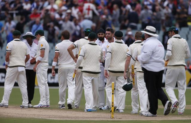 England's James Anderson and Monty Panesar (both C, facing camera) shake hands with the Australia team after losing the second Ashes cricket test at the Adelaide Oval December 9, 2013. Australia captured England's four remaining wickets before lunch to close out an emphatic 218-run victory in the second Ashes test on Monday. REUTERS/David Gray (AUSTRALIA - Tags: SPORT CRICKET)