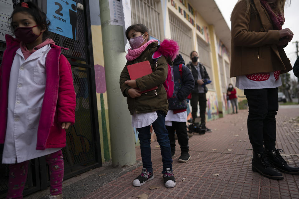 Children stand in line to enter their elementary school in San Martin, a municipality in the Buenos Aires province, Argentina, Wednesday, June 16, 2021. More than 3 million students in the Buenos Aires province resumed in-person classes at all levels Wednesday amid a severe, second wave of the COVID-19 pandemic. (AP Photo/Victor R. Caivano)