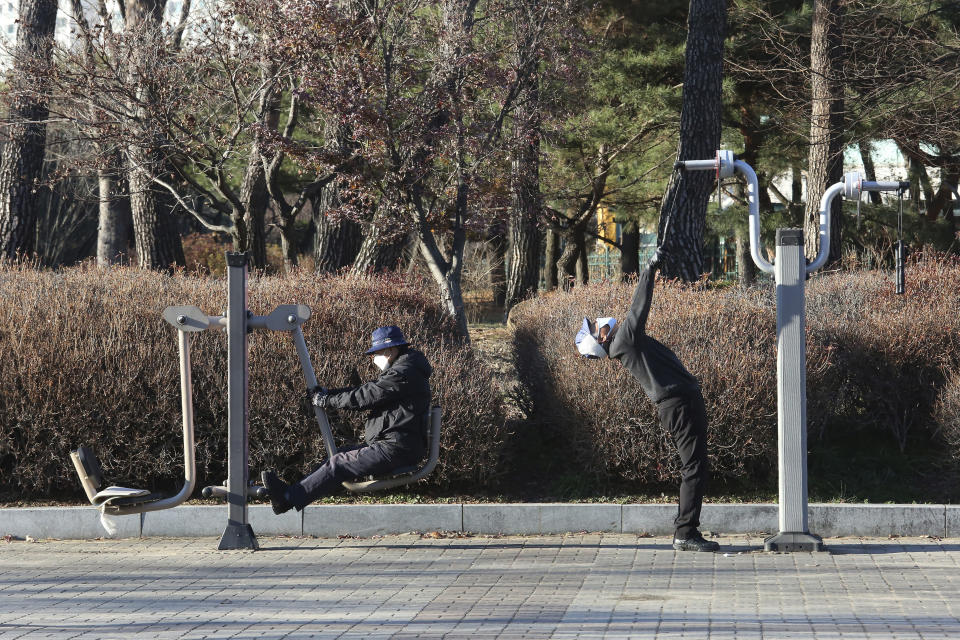 People wearing face masks as a precaution against the coronavirus exercise at a park at a park in Goyang, South Korea, Friday, Dec. 4, 2020. The Korea Disease Control and Prevention Agency said Friday that 600 of the newly confirmed patients were domestically transmitted cases — nearly 80% of them in the densely populous Seoul area, which has been at the center of a recent viral resurgence. (AP Photo/Ahn Young-joon)
