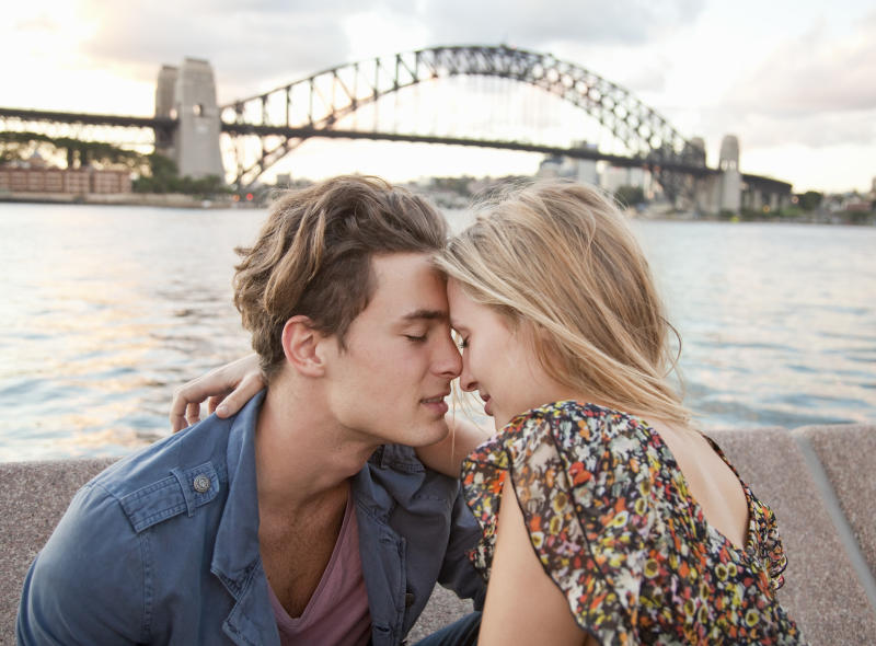 Couple embrace in front of Sydney Harbour Bridge