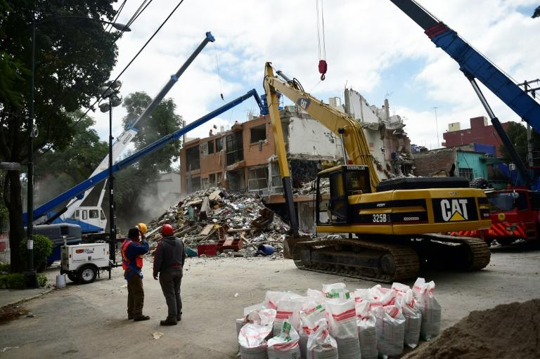 Technicians watch as a building seriously damaged by the September 19 earthquake is demolished in Mexico City on October 17, 2017