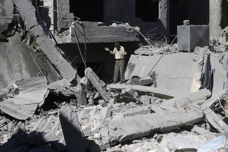 A man reacts amid rubble from what activists said was barrel bombs dropped by forces loyal to Syria's President Bashar Al-Assad in Douma, eastern Ghouta, near Damascus, Syria August 22, 2015. REUTERS/Bassam Khabieh - RTS6ALL