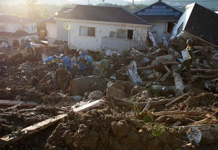 Rescue workers and Japan Self-Defense Forces soldiers search for missing people at a landslide site caused by heavy rain in Kumano Town, Hiroshima Prefecture, Japan July 11, 2018. REUTERS/Issei Kato