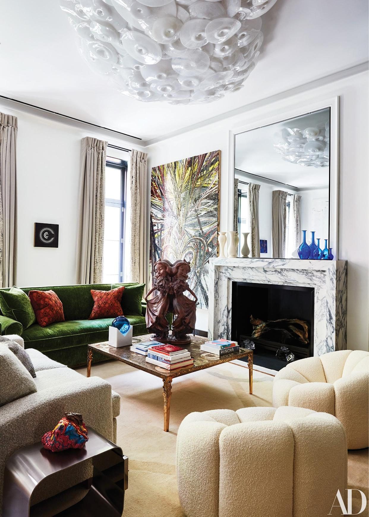 """<div class=""""caption""""> The art-filled living room is decorated with custom sofas and a pair of Pierre Paulin chairs. A Paul McCarthy sculpture sits atop a cocktail table by Ingrid Donat; Maria Pergay side table. </div>"""