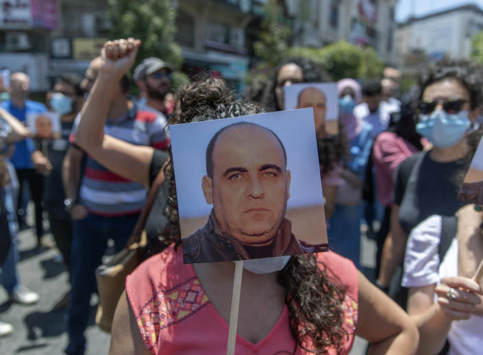 Angry demonstrators carry pictures of Nizar Banat, an outspoken critic of the Palestinian Authority, and chant anti-PA slogans during a rally protesting his death, in the West Bank city of Ramallah, Thursday, June 24, 2021. Banat who was a candidate in parliamentary elections called off earlier this year died after Palestinian security forces arrested him and beat him with batons on Thursday, his family said. (AP Photo/Nasser Nasser)