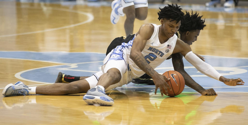 North Carolina's Caleb Love (2) secures a loose ball from College of Charleston's Zep Jasper (12) during the first half of an NCAA college basketball game Wednesday, Nov. 25, 2020, in Chapel Hill, N.C. (Robert Willett/The News & Observer via AP, Pool)
