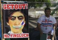 An anti-government protester stands next to a defaced image of Thailand's Prime Minister Yingluck Shinawatra during a rally near the Government Complex in Bangkok February 18, 2014. Gun battles erupted between Thai police and anti-government protesters in Bangkok on Tuesday and three people were killed and dozens wounded as authorities made their most determined effort yet to clear demonstrators from the streets. REUTERS/Chaiwat Subprasom (THAILAND - Tags: POLITICS CIVIL UNREST)
