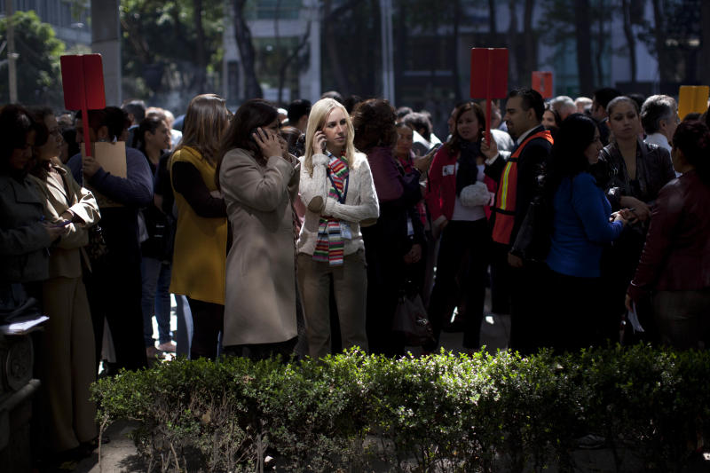 People gather in the street after evacuating their office buildings after an earthquake was felt in Mexico City, Wednesday, Nov. 7, 2012.  A strong earthquake struck off the Pacific coast of Guatemala on Wednesday morning, rocking the capital and shaking buildings as far away as Mexico City and El Salvador. (AP Photo/Alexandre Meneghini)