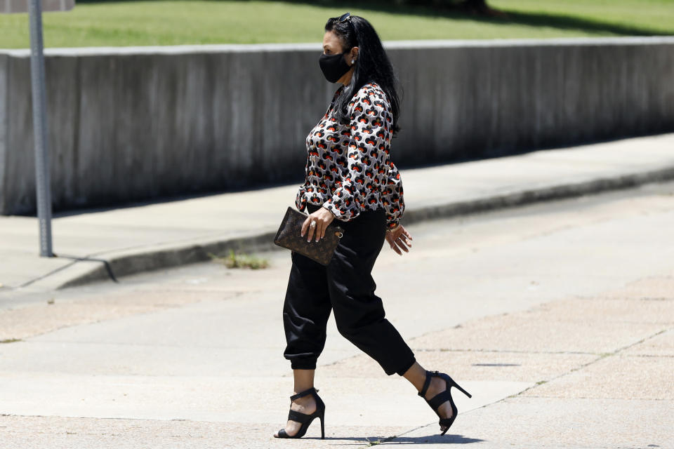 Iris Villalon, 44, of Ocean Springs, crosses the street as she heads for the Thad Cochran United States Courthouse in Jackson, Miss., Thursday, Aug. 6, 2020, for an arraignment hearing in federal court on immigration crimes and other federal charges stemming from the largest single-state worksite enforcement action last year at a number of Mississippi poultry processing plants. (AP Photo/Rogelio V. Solis)