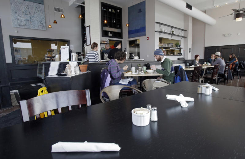 In this Tuesday, Jan. 28, 2014 photo, customers eat lunch at Bonbon Pastry and Cafe in Cleveland. Single-digit temperatures across the U.S. and record snowfalls in the Midwest since the beginning of January have put the freeze on businesses that rely on walk-ins and appointments. At the cafe in the city's Market Square district, this past weekend was especially slow with whiteout conditions making going outside unappealing for customers. (AP Photo)