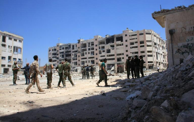 Syrian army soldiers patrol the area around the entrance of Bani Zeid after seizing the district of Leramun, on the northwest outskirts of Aleppo, from rebels on July 28, 2016