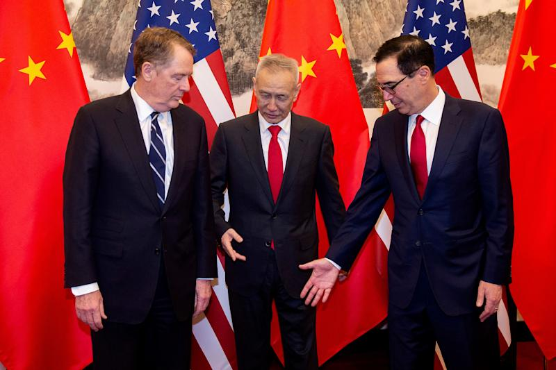 China's Vice Premier Liu He, center, gestures with U.S. Treasury Secretary Steven Mnuchin, right, as U.S. Trade Representative Robert Lighthizer looks on as they pose for a photo at Diaoyutai State Guesthouse in Beijing Friday, March 29, 2019. (Nicolas Asfouri/Pool Photo via AP)