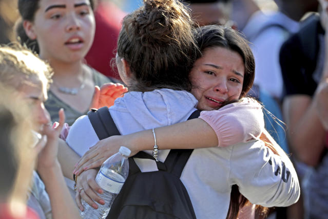 Students released from a lockdown embrace following a shooting at Marjory Stoneman Douglas High School in Parkland, Fla., Wednesday, Feb. 14, 2018. (John McCall/South Florida Sun-Sentinel via AP)