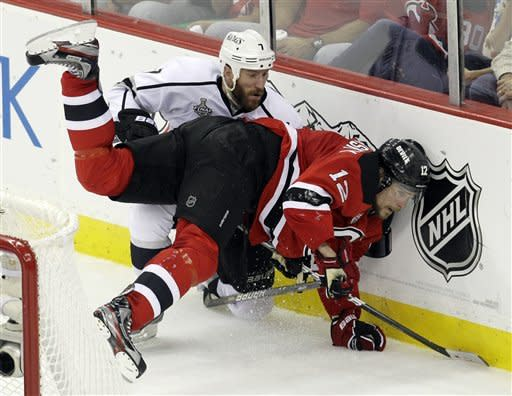 Los Angeles Kings' Rob Scuderi, left, and New Jersey Devils' Alexei Ponikarovsky, of Ukraine, collide behind the goal during the second period of Game 2 of the NHL hockey Stanley Cup finals on Saturday, June 2, 2012, in Newark, N.J. (AP Photo/Kathy Willens)