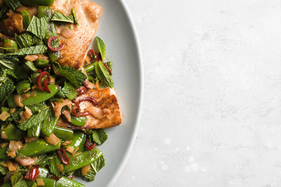 This image released by Milk Street shows a recipe for salmon with chilies, pickled ginger and snap peas. (Milk Street via AP)