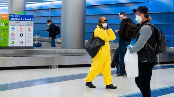 PHOTO: A person wearing plastic coveralls and mask waits for their luggage at Terminal 7 at Los Angeles International Airport (LAX) during the outbreak of the novel coronavirus, which causes COVID-19, April 16, 2020, in Los Angeles. (Valerie Macon/AFP via Getty Images)