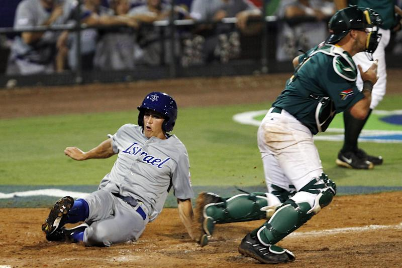 Israel's Adam Greenberg, left, slides safely into home plate after scoring on a base hit by Shawn Green as South Africa catcher Kyle Botha, right, awaits the throw in the ninth inning of a World Baseball Classic qualifier baseball game in Jupiter, Fla., Wednesday, Sept. 19, 2012. Israel won 7-3. (AP Photo/Alan Diaz)