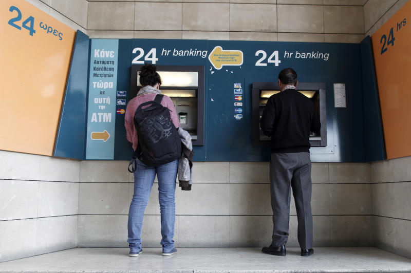 People use ATMs outside a closed branch of the Bank of Cyprus in capital Nicosia, Cyprus, Wednesday, March 27, 2013. Cypriot authorities are preparing limits on how much money depositors can take out of their accounts a day before banks are set to reopen. (AP Photo/Petros Giannakouris)