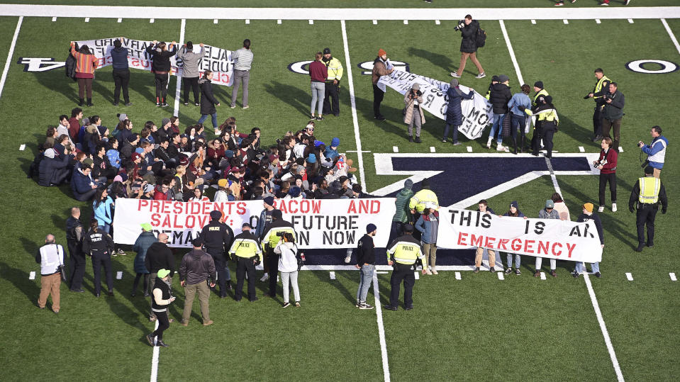 Demonstrators stage a climate change protest at the Yale Bowl delaying the start of the second half of an NCAA college football game between Harvard and Yale Saturday, Nov. 23, 2019, in in New Haven, Conn. (Arnold Gold/New Haven Register via AP)