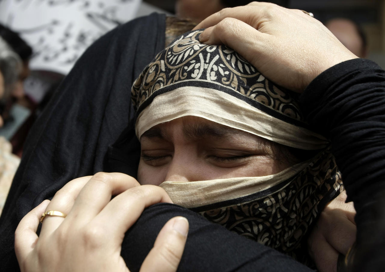Family members of Pakistani acid attack victim Fakhra Younnus, mourn her death at Karachi airport in Pakistan on Sunday, March 25, 2012. Fakhra who committed suicide by jumping from the sixth floor of her flat in Rome, was a victim of an acid attack allegedly carried out 12 years ago by her husband, the son of a feudal politician. (AP Photo)