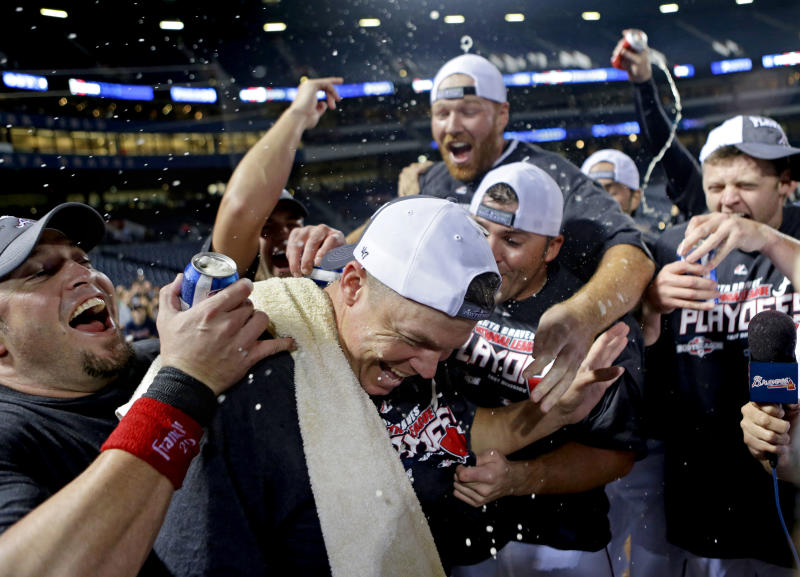 Atlanta Braves' Eric Hinske, left, and Chipper Jones, front center, celebrate with teammates after the Braves beat the Miami Marlins 4-3 in a baseball game to clinch at least an NL wild-card berth, Tuesday, Sept. 25, 2012, in Atlanta. (AP Photo/David Goldman)