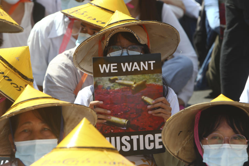"""An anti-coup protester holds a sign that reads: """"We Want Justice"""" along with an image showing bullet casings on a pool of blood during a rally near the Mandalay Railway Station in Mandalay, Myanmar, Monday, Feb. 22, 2021. A call for a Monday general strike by demonstrators in Myanmar protesting the military's seizure of power has been met by the ruling junta with a thinly veiled threat to use lethal force, raising the possibility of major clashes. (AP Photo)"""