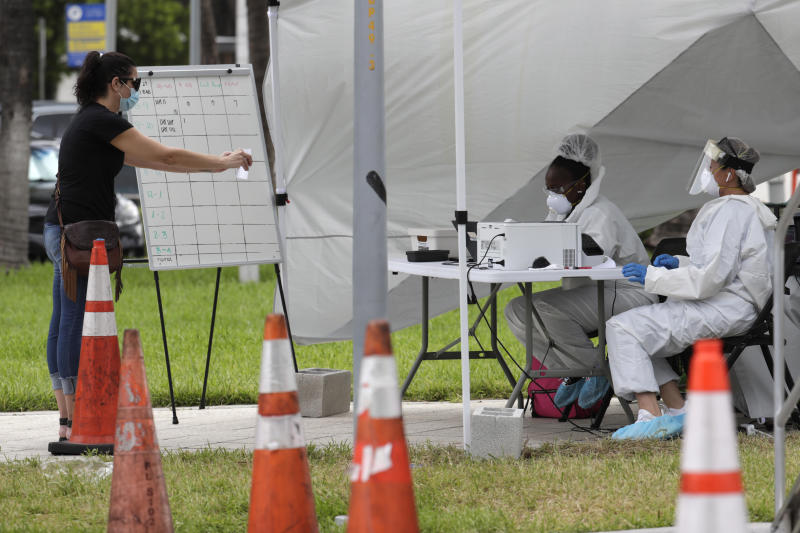 Health care workers take information from people in line at a walk-up COVID-19 testing site during the coronavirus pandemic, Friday, July 17, 2020, in Miami Beach, Fla. The mobile testing truck is operated by Aardvark Mobile Health, which has partnered with the Florida Division of Emergency Management. People getting tested are separated from nurses via a glass pane. (AP Photo/Lynne Sladky)