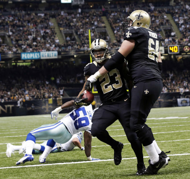 New Orleans Saints running back Pierre Thomas (23) crosses into the end zone for a touchdown between tackle Zach Strief (64) and Dallas Cowboys inside linebacker Ernie Sims (59) in the first half of an NFL football game in New Orleans, Sunday, Nov. 10, 2013. (AP Photo/Dave Martin)