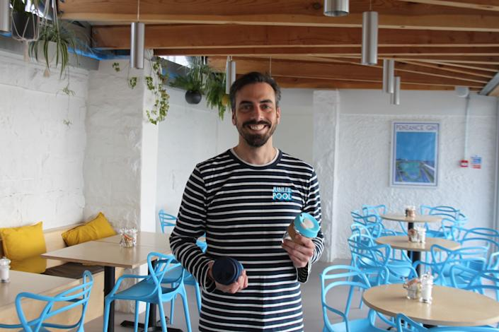 Sam Dean at the Jubilee Café in Penzance with some of the reusable glass coffee cups he sells. (Photo: Anna Turns)