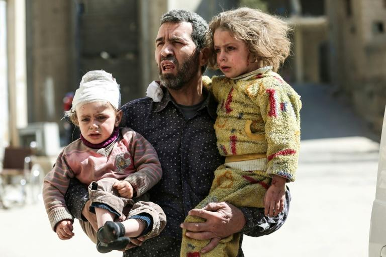 A Syrian man carries two injured children after a reported air strike in the rebel-controlled town of Hammuriyeh, on the outskirts of the capital Damascus, on March 25, 2017