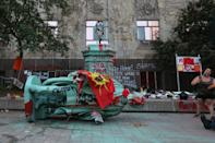 <p>The toppled statue of Egerton Ryerson, one of the architects of indigenous boarding school system, is laying on its side in Toronto on June 6, 2021. (Steve Russell/Toronto Star via Getty Images)</p>