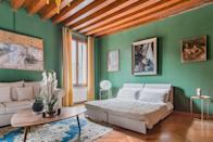 """Green really seems to be Venice's color, doesn't it? This one-bedroom apartment has a Murphy bed in the living room (pictured), well-equipped kitchen, washer/dryer, and all of the amenities of an <a href=""""https://www.cntraveler.com/story/airbnb-plus-is-for-people-who-hate-airbnb?mbid=synd_yahoo_rss"""" rel=""""nofollow noopener"""" target=""""_blank"""" data-ylk=""""slk:Airbnb Plus"""" class=""""link rapid-noclick-resp"""">Airbnb Plus</a>, like strong Wi-Fi, a coffee maker, and more. There's also a high chair and crib available upon request (though no bathtub). While centrally located—just a 10-minute walk from St. Marks Plaza—the home is on a piazza's side street, meaning noise levels in the apartment are low even though the city's most popular attractions are just steps outside. $166, Airbnb (Starting Price). <a href=""""https://www.airbnb.com/rooms/plus/28078000"""" rel=""""nofollow noopener"""" target=""""_blank"""" data-ylk=""""slk:Get it now!"""" class=""""link rapid-noclick-resp"""">Get it now!</a>"""