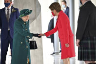 Britain's Queen Elizabeth II is greeted by Scotland's First Minister Nicola Sturgeon, right, as she arrives at the Scottish Parliament to deliver a speech in the debating chamber to mark the official start of the sixth session of Parliament, in Edinburgh, Scotland, Saturday Oct. 2, 2021. (Jeff J Mitchell/PA via AP)