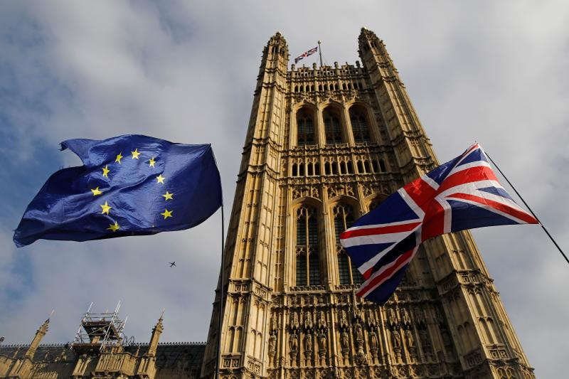 EU and Union flags flutter in the breeze outside the Houses of Parliament in Westminster, central London on October 17, 2019. - Britain's Prime Minister Boris Johnson and the European Union on Thursday reached a provisional agreement that might just see Britain leave the European Union by the October 31 deadline. (Photo by Tolga AKMEN / AFP) (Photo by TOLGA AKMEN/AFP via Getty Images)