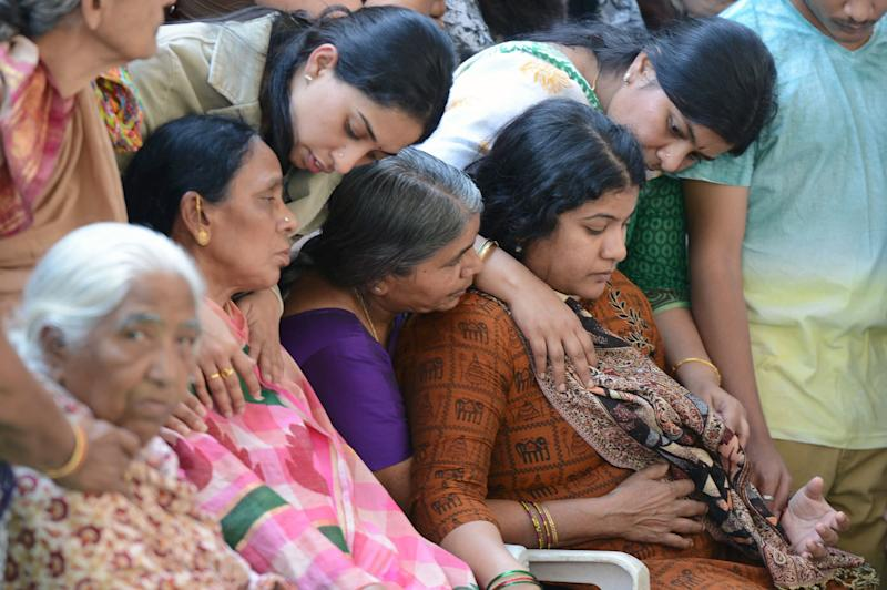 Sunayana Dumala (R), wife of killed Indian engineer Srinivas Kuchibhotla, who was shot dead in the US state of Kansas, is consoled by family members prior to performing the last rites at his funeral in Hyderabad on February 28, 2017. (NOAH SEELAM via Getty Images)