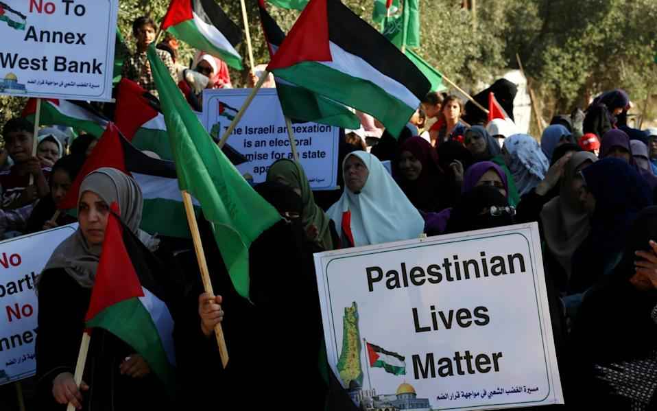 Hamas supporters wave their green and national flags during a protest against Israel's plan to annex parts of the West Bank - Adel Hana/AP