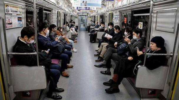 PHOTO: People wearing face masks amid concerns over the spread of the novel coronavirus commute on a train in Tokyo, Japan, on April 6, 2020. (Behrouz Mehri/AFP via Getty Images)