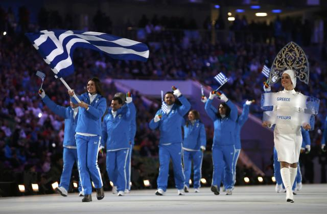 Greece's flag-bearer Panagiota Tsakiri leads her delegation as they march in during the opening ceremony of the 2014 Sochi Winter Olympics, February 7, 2014. REUTERS/Jim Young (RUSSIA - Tags: OLYMPICS SPORT)