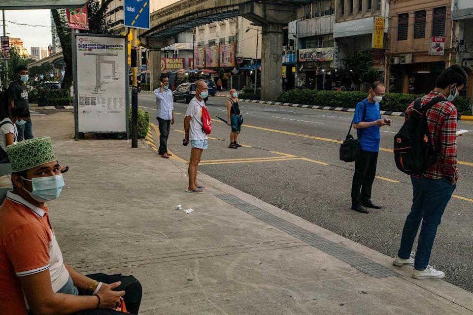 People wearing face masks as a precaution against the spread of Covid-19 wait for a bus in Kuala Lumpur May 31, 2021. — Picture by Firdaus Latif