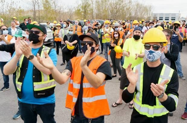 Striking Port of Montreal dockworkers applaud speeches during Thursday's rally in Montreal.