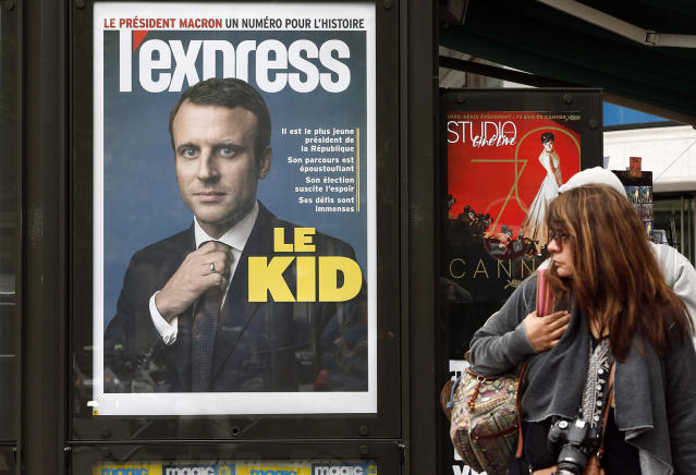 <p>A woman looks toward a poster of the front cover of L'Express, with the picture of the newly elected French President Emmanuel Macron, in Paris, May 8, 2017. Macron defeated far-right leader Marine Le Pen in Sunday's presidential vote. (Chesnot/Getty Images) </p>