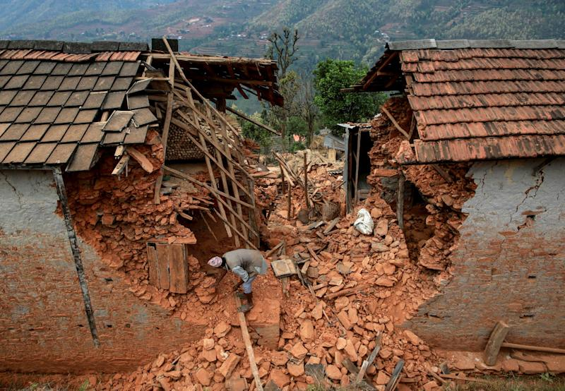 Resident tries to clear debris of his house at a village following Saturday's earthquake in Sindhupalchowk