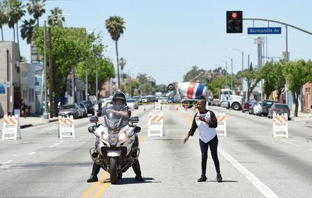 A protester takes direction from an Los Angeles Police Department officer at the intersection of Florence and Normandie Avenue, the flashpoint where the riots started 25 years ago, during a march and rally to remember and honor the victims of the 1992 Los Angeles riots in Los Angeles, California, U.S., April 29, 2017. REUTERS/Kevork Djansezian