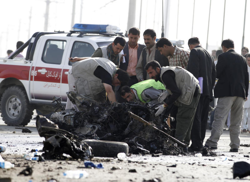Afghan investigators inspect the wreckage of a suicide bomber's car Tuesday, Sept. 18, 2012 in Kabul, Afghanistan. A suicide bomber rammed a car packed with explosives into a mini-bus carrying foreign aviation workers to the airport in the Afghan capital early Tuesday, killing at least nine people in an attack a militant group said was revenge for an anti-Islam film that ridicules the Prophet Muhammad. (AP Photo/Ahmad Jamshid)