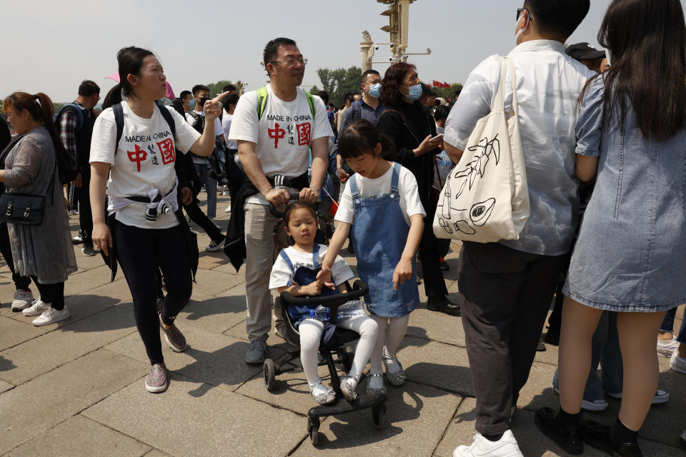 """Residents wearing t-shirts which reads """"Made In China"""" visit Tiananmen Gate with two children in Beijing on May 3, 2021. China's population growth is falling closer to zero as fewer couples have children, the government announced Tuesday, May 11, 2021, adding to strains on an aging society with a shrinking workforce. (AP Photo/Ng Han Guan)"""